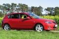Roter Mazda3 vor einem Rapsfeld.